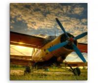 Leinwandbild Flugzeug Doppeldecker vorn mit Propeller bei Sonnenaufgang